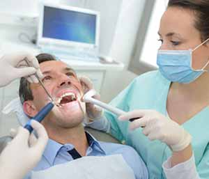 Image of a Patient sitting on the chair, Dentist & assistant checking patient's mouth
